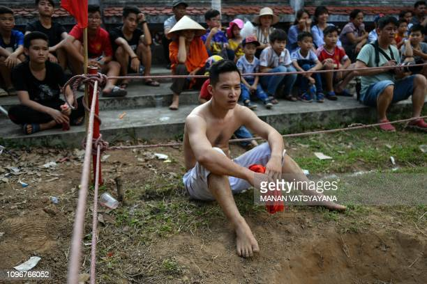 This photograph taken on February 9 2019 shows a Vietnamese man taking a break after wrestling for the prized jackfruit wooden ball during the...
