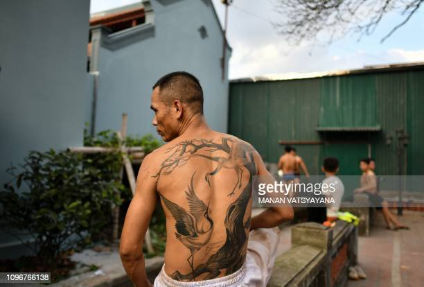 This photograph taken on February 9 2019 shows a Vietnamese man cleaningup after wrestling for the prized jackfruit wooden ball during the...