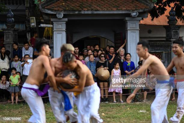 This photograph taken on February 9 2019 shows locals watching as men wrestle for the prized jackfruit wooden ball during the traditional 'Vat Cau'...