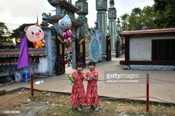 This photograph taken on February 9 2019 shows two young Vietnamese girls standing in an empty area after the traditional 'Vat Cau' or ball wrestling...