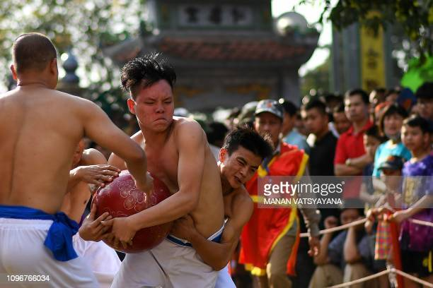 This photograph taken on February 9 2019 shows Vietnamese men wrestling for the prized jackfruit wooden ball during the traditional 'Vat Cau' or ball...