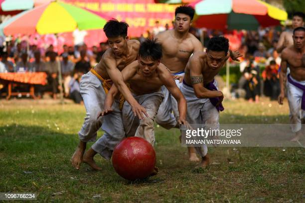 TOPSHOT This photograph taken on February 9 2019 shows Vietnamese men wrestling for the prized jackfruit wooden ball during the traditional 'Vat Cau'...
