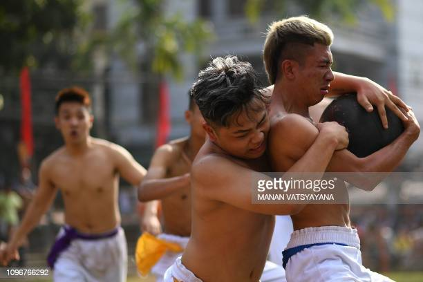 TOPSHOT This photograph taken on February 9 2019 shows Vietnamese men competing for the prized jackfruit wooden ball during the traditional 'Vat Cau'...