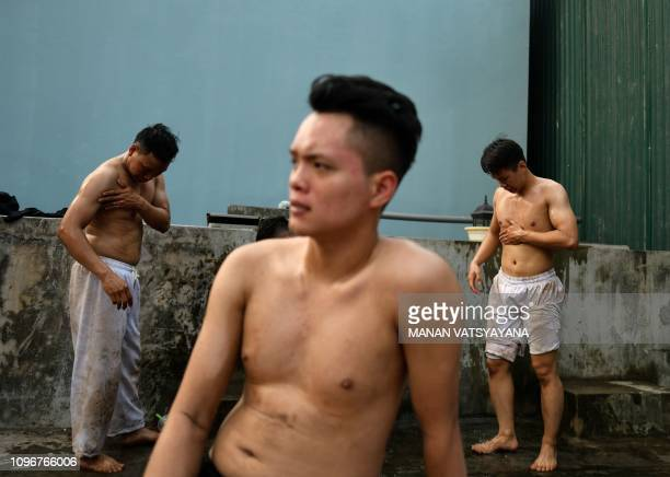 TOPSHOT This photograph taken on February 9 2019 shows Vietnamese men cleaning up after wrestling for a prized jackfruit wooden ball during the...