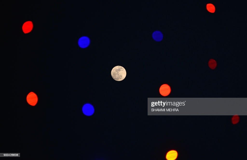 TOPSHOT - This photograph taken on January 1, 2018, shows a 'supermoon' rising in the sky next to decorative lights in Jalandhar. / AFP PHOTO / Shammi MEHRA