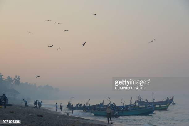 TOPSHOT This photograph taken on January 10 2018 shows Indian fishermen moving their traditional boat early morning on Marari beach in the Indian...