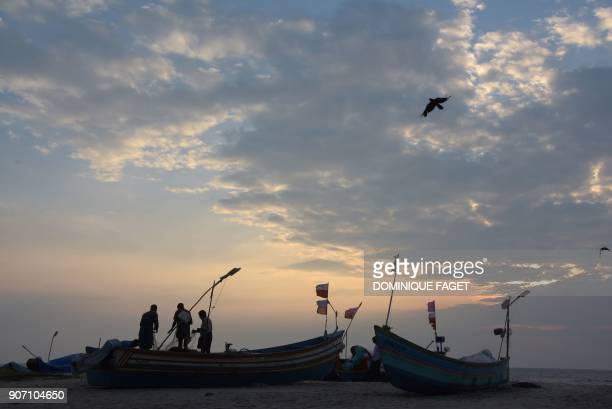 This photograph taken on January 10 2018 shows Indian fishermen cleaning their nets early in the morning on Marari beach in the Indian state of...