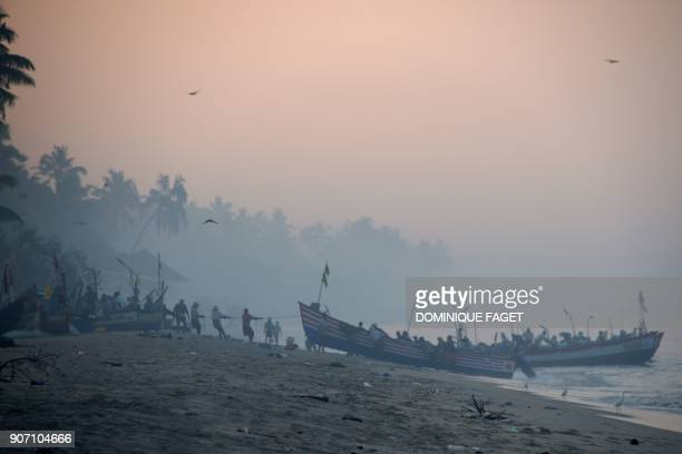 This photograph taken on January 10 2018 shows Indian fishermen moving their traditional boats early in the morning on Marari beach in the Indian...