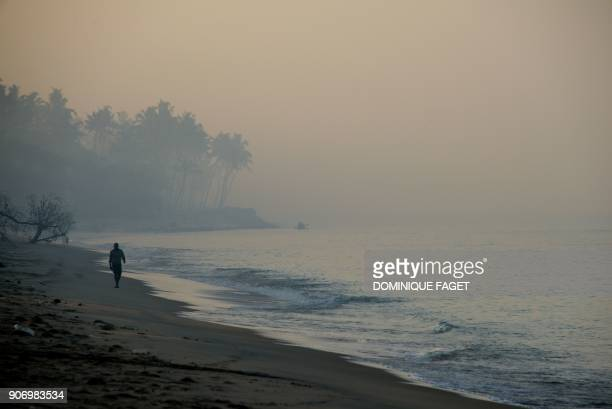 TOPSHOT This photograph taken on January 11 2018 shows a tourist walking along Marari beach in the state of Kerala / AFP PHOTO / DOMINIQUE FAGET