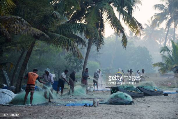This photograph taken on January 11 2018 shows Indian fishermen cleaning their nets early morning on Marari beach in the Indian state of Kerala FAGET