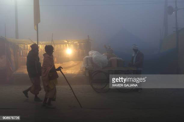 TOPSHOT This photograph taken on January 14 2018 shows Indian devotees walking along the camp area at Sangam the confluence of the rivers Ganges...
