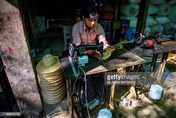 This photograph taken on January 17 2020 shows a woman sewing traditional straw hats a home industry in the village of Lekkapin some 80 kilometers...