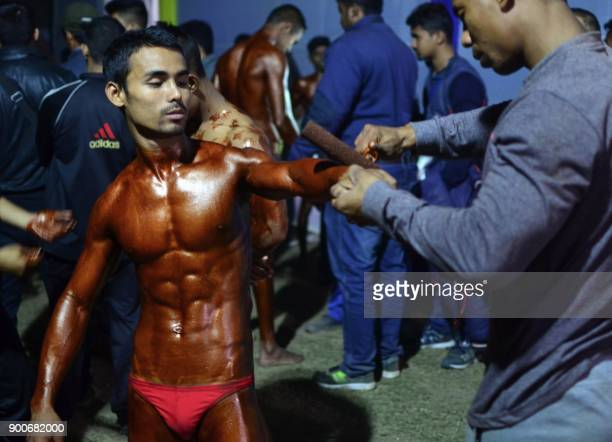 This photograph taken on January 2 2018 shows an Indian bodybuilding competitor getting a tanning product applied to his body ahead of the All Assam...