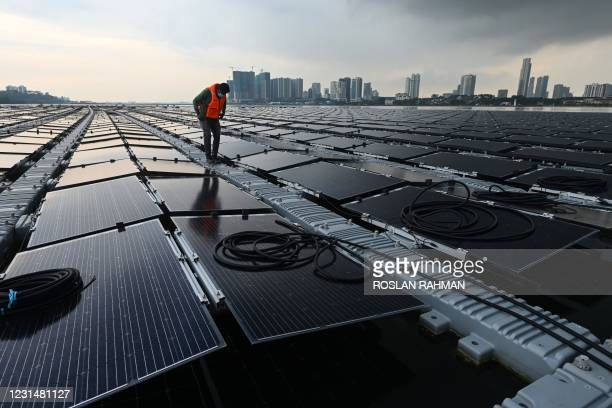 This photograph taken on January 22, 2021 shows a worker checking cables on a floating solar power farm at sea, off Singapore's northern coast just...