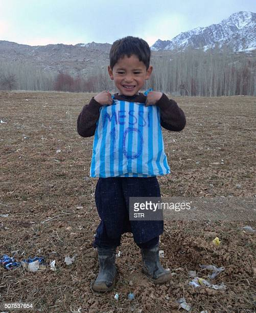 This photograph taken on January 24 2016 and provided by the family of Afghan boy and Lionel Messi fan Murtaza Ahmadi with his plastic bag jersey in...