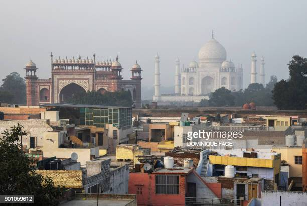This photograph taken on January 3 2018 shows residential buildings next to the Taj Mahal in Agra India is to restrict the number of daily visitors...