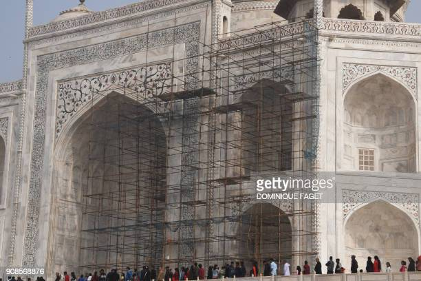 This photograph taken on January 3, 2018 shows tourists visiting the Taj Mahal near scaffolding installed for the conservation work at the monument...