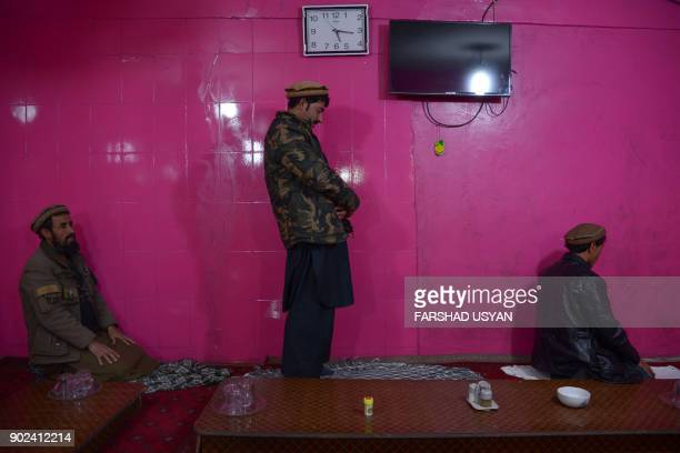 TOPSHOT This photograph taken on January 7 shows Afghan men praying in a local restaurant in MazariSharif USYAN