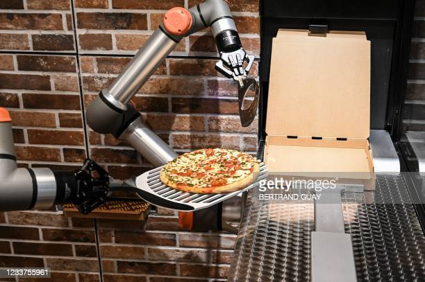 """This photograph taken on July 1 shows """"Pazzi"""", a pizza-making robot at work in a restaurant in Paris. - The pizza-making robot from Parisian startup..."""