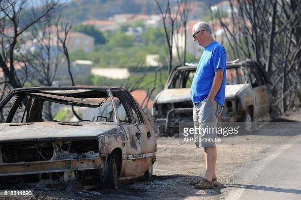 This photograph taken on July 19 shows a car owner looking at his burned out vehicle in village of Kucine near the Adriatic coastal town of Split...