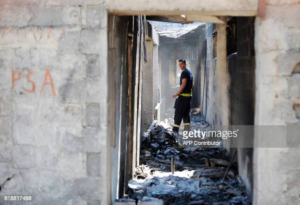 This photograph taken on July 19 shows a firefighter as he walks in a burntout house in the village of Zrnovnica near the Adriatic coastal town of...