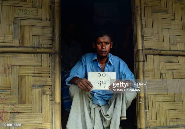 This photograph taken on July 20 2018 shows Rohingya refugee Jalal Ahmed with his old house number plate in Jamtoli refugee camp in Ukhia in the...