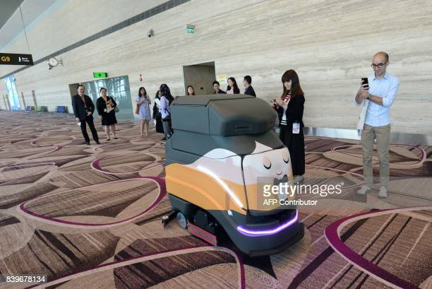 This photograph taken on July 25 2017 shows journalists watching an automatic robot vacuum cleaning the floor during a media tour at the newly built...