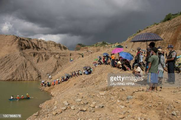 This photograph taken on July 25 2018 shows onlookers during the search and rescue operation for miners after a landslide at a jade mining area in...