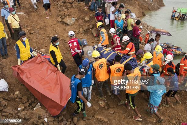 This photograph taken on July 26 2018 shows search and rescue volunteers carrying the body of miner after a landslide at a jade mining area in...