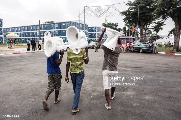This photograph taken on July 27 shows men carrying toilets as they walk down a street in Abidjan / AFP PHOTO / Armend NIMANI