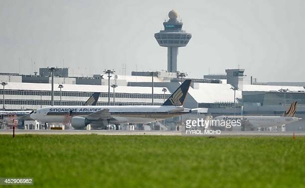 This photograph taken on July 29 2014 shows a Singapore Airlines passenger plane parked at a terminal next to a Tiger Air plane at Changi...
