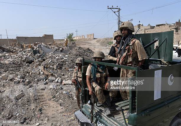 This photograph taken on July 9 2014 shows Pakistani soldiers patrol past destroyed militants' hideouts during a military operation against Taliban...