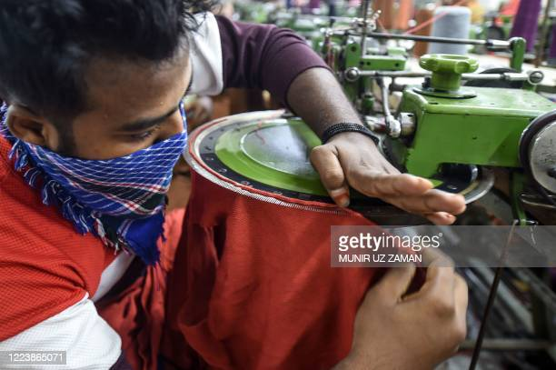 This photograph taken on June 18, 2020 shows a labourer working at a garment factory as it has reopened after being close during a lockdown imposed...