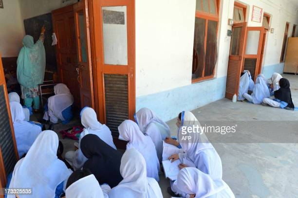This photograph taken on June 21 2013 shows Pakistani girls sitting outside the doors of a classroom as they attend class at a school in Mingora the...