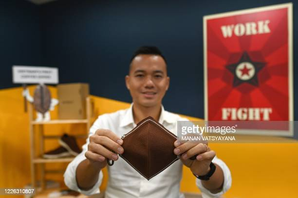 This photograph taken on June 29, 2020 shows entrepreneur Le Thanh, managing director of ShoeX, posing with a face mask made from coffee grounds at...