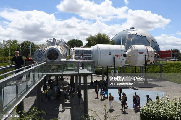 This photograph taken on June 29 shows visitors walking in front of a model of the Russian Space Station Mir at the Cite de l'Espace theme park in...