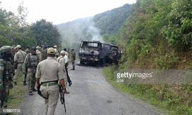 This photograph taken on June 4 2015 shows Indian security personnel and smoldering vehicle wreckage at the scene of an attack on a military convoy...