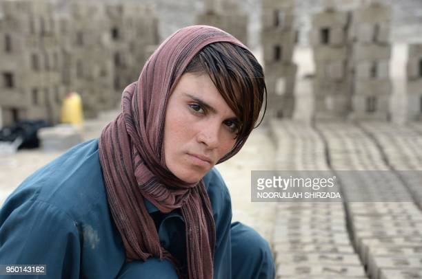 This photograph taken on March 11 2018 shows Afghan female labourer Sitara Wafadar who dresses as a male in order to support her family posing for a...