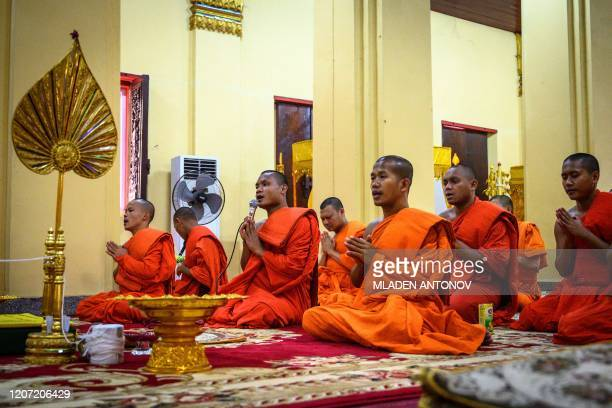 This photograph taken on March 12, 2020 shows Buddhist monks praying at a temple in Vientiane.