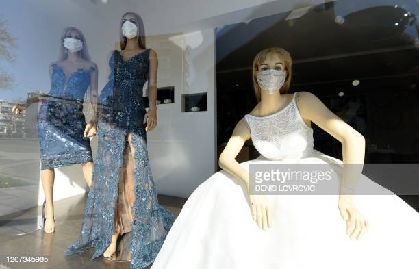 This photograph taken on March 16 shows mannequins with protective masks in the display window of a famous bridal dresses store in Zagreb amid the...