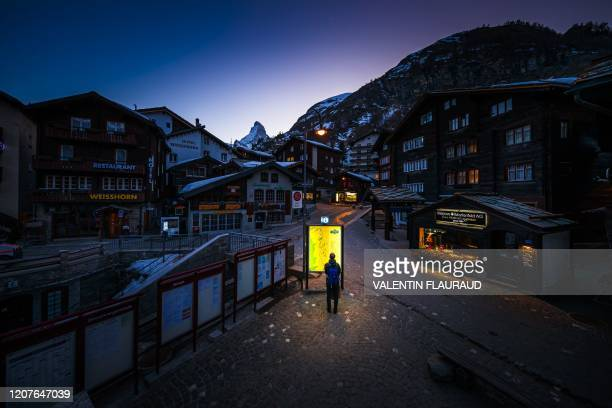 This photograph taken on March 18 shows a pedestrian looking at an illuminated map board in the empty streets of the Alpine resort of Zermatt, with...