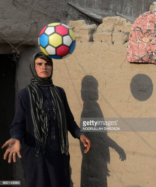 This photograph taken on March 20 2018 shows Afghan female labourer Sitara Wafadar who dresses as a male in order to support her family playing with...