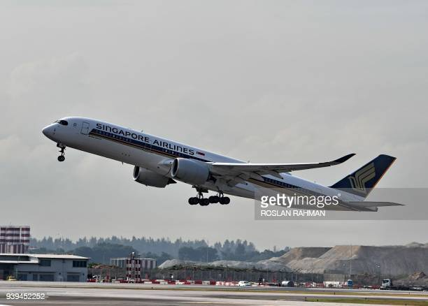 This photograph taken on March 28 2018 shows a Singapore Airlines Airbus A350 aircraft taking off from Singapore Changi Airport / AFP PHOTO / Roslan...