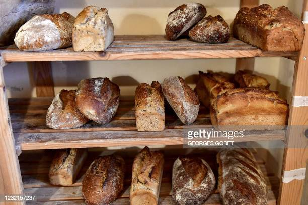 """This photograph taken on March 30, 2021 shows bread loaves on a shelf at Remi Cauvin's bakery """"La couleur des bles"""", specialised in sourdough bread..."""