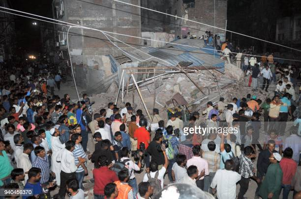 This photograph taken on March 31 2018 shows Indian onlookers gathering near the rubble of a building after the structure collapsed in Indore in the...