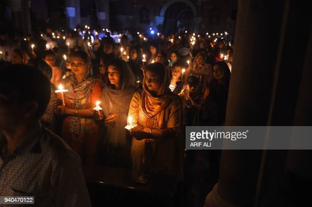 This photograph taken on March 31, 2018 shows Pakistani Christian devotees holding candles while attending a Easter vigil mass at the Sacred Heart...
