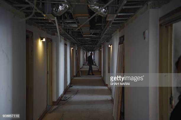 This photograph taken on March 7 2018 shows an Afghan man walking along a corridor of the Intercontinental Hotel in Kabul Richard Clayderman's...