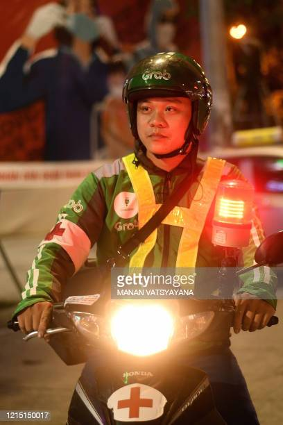 This photograph taken on May 12, 2020 shows Grab motorcycle rider Pham Quoc Viet posing during a night patrol to help traffic accident victims on the...