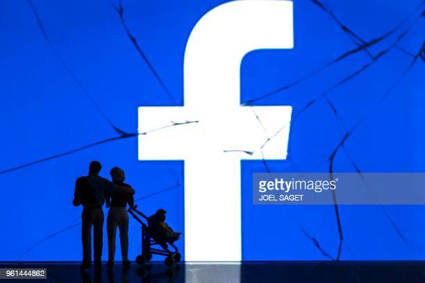 This photograph taken on May 16 shows figurines standing in front of the logo of social network Facebook on a cracked screen of a smartphone in Paris.