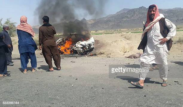 This photograph taken on May 21 2016 shows Pakistani local residents gathering around a destroyed vehicle hit by a drone strike in which Afghan...